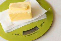 Stück Butter auf Küchenskala Lizenzfreie Stockbilder