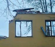 Stück der Wand des ruinierten Hauses mit zerbrochenen Fensterscheiben, Abbau des Gebäudes Stockbilder