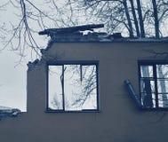 Stück der Wand des ruinierten Hauses mit zerbrochenen Fensterscheiben, Abbau des Gebäudes Lizenzfreies Stockbild