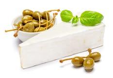 Stück des Briekäses oder des camambert Käses und der Kapriolen auf einem weißen Hintergrund Lizenzfreies Stockbild