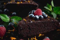 Stück des dunklen Schokoladenkuchens verziert mit Himbeeren Stockfotos