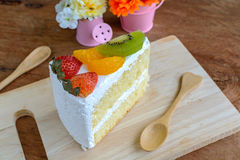 Stück des Fruchtkuchens mit Kiwi, Erdbeere und Orange Stockbild