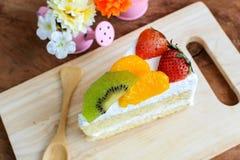 Stück des Fruchtkuchens mit Kiwi, Erdbeere und Orange Stockfotografie