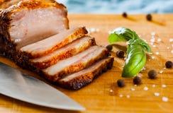 Stück des gebratenen Schweinebauchs auf hölzernem Schneidebrett Lizenzfreies Stockfoto