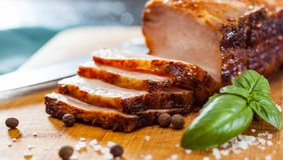 Stück des gebratenen Schweinebauchs auf hölzernem Schneidebrett Lizenzfreies Stockbild