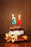 Stück des Geburtstags-Kuchens mit brennender Kerze als Nr. dreißig Stockbild