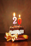 Stück des Geburtstags-Kuchens mit brennender Kerze als Nr. zwanzig Stockfotos