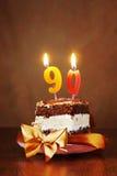 Stück des Geburtstags-Schokoladen-Kuchens mit brennender Kerze als Zahl Stockbild