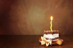 Stück des Geburtstagsschokoladenkuchens mit einer brennenden Kerze Stockfotos