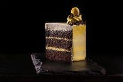 Stück des gelben Geburtstagskuchens Dekorative Sahnedekorationen auf dem Kuchen Schwarzer Hintergrund Stockbilder