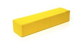 Stück des gelben hölzernen Bauklotzes auf Weiß Stockfoto