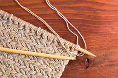 Stück des gestrickten Stoffes mit hölzernen Nadeln auf Holztisch Lizenzfreie Stockfotos