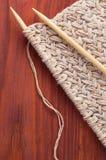 Stück des gestrickten Stoffes mit hölzernen Nadeln auf Holztisch Lizenzfreies Stockfoto