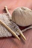 Stück des gestrickten Stoffes mit Threads und hölzernen Nadeln auf Holztisch Stockfotos