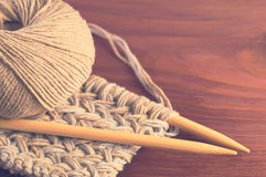 Stück des gestrickten Stoffes mit Threads und hölzernen Nadeln auf Holztisch Lizenzfreies Stockbild