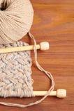 Stück des gestrickten Stoffes mit Threads und hölzernen Nadeln auf Holztisch Lizenzfreie Stockfotografie