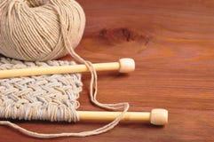 Stück des gestrickten Stoffes mit Threads und hölzernen Nadeln auf Holztisch Stockfotografie