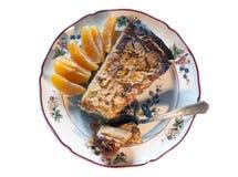Stück des handgemachten Kuchens mit den Mandeln und Orangenkeilen lokalisiert auf Weiß Stockbild