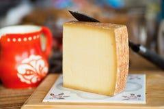 Stück des Käses, des Messers und des roten Pitchers Stockbild