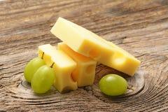 Stück des Käses und der Traube auf Holztisch Stockfotos