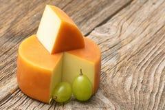 Stück des Käses und der Traube auf Holztisch Stockbild