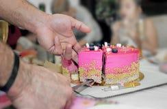 Stück des Kuchens auf der Platte schnitt Männer ` s Hände ab Lizenzfreie Stockfotos