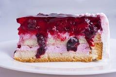 Stück des Kuchens mit Beeren auf einer Platte Stockbild