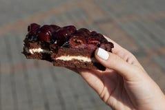 Stück des Kuchens mit Kirschen in der Mädchen ` s Hand auf der Straße lizenzfreies stockfoto
