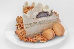 Stück des Kuchens mit Muttern und Sahne Stockfotografie
