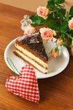 Stück des Kuchens und rotes Herz auf hölzernem Hintergrund Rote Rose Lizenzfreie Stockfotografie