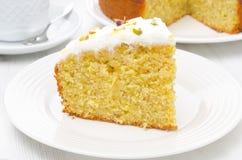Stück des orange Kuchens mit griechischem Jogurt, Honig und Pistazien Lizenzfreie Stockbilder