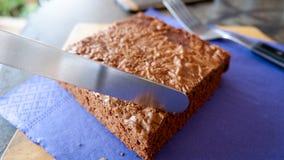 Stück des Schokoladenkuchenkuchens, der mit einem Messer geschnitten wird stockfotos