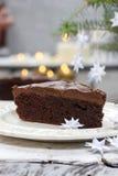 Stück des Schokoladenkuchens im weißes Weihnachtsgedeck Stockbild