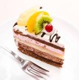 Stück des Schokoladenkuchens mit Frucht auf Platte Stockbild