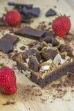 Stück des Schokoladenkuchens mit Schokolade und einigen Erdbeeren auf dem hölzernen Hintergrund Stockfotografie