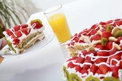 Stück des selbst gemachten Kuchens wird mit Orangensaft gedient Stockbilder