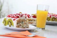 Stück des selbst gemachten Kuchens wird mit Orangensaft gedient Stockfoto