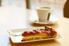 Stück des Walderdbeerekuchens und der Schale Espressos im Café Lizenzfreie Stockfotografie