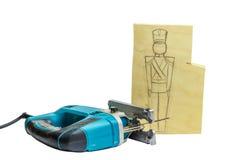Stück Holz mit einer Bleistift-Zeichnung eines Soldaten und der Laubsäge Lizenzfreie Stockfotos
