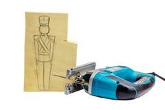 Stück Holz mit einer Bleistift-Zeichnung eines Soldaten und der Laubsäge Lizenzfreie Stockfotografie