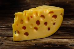 Stück Käse auf Holztisch Stockfotografie