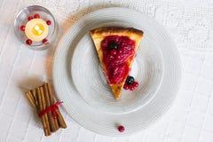 Stück Käsekuchen mit den roten und schwarzen Beeren auf es auf weißer Platte mit Zimtstangen Stockfotos