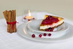 Stück Käsekuchen mit den roten und schwarzen Beeren auf es auf weißer Platte mit Zimtstangen Lizenzfreie Stockbilder