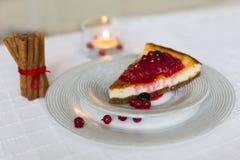 Stück Käsekuchen mit den roten und schwarzen Beeren auf es auf weißer Platte mit Zimtstangen mit roter Schnur und brennender Kerz Lizenzfreies Stockbild