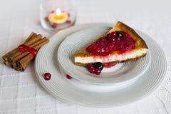 Stück Käsekuchen mit den roten und schwarzen Beeren auf es auf weißer Platte mit Zimtstangen mit roter Schnur und brennender Kerz Stockbild