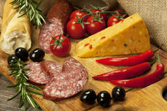 Stück natürlicher Käse und Salami auf einem hölzernen Brett Stockfotos