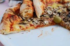 Stück Pilzpizza auf weißer Platte Stockbilder