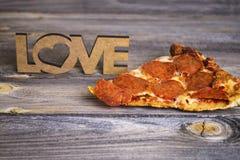 Stück Pizza auf einem alten hölzernen Hintergrund Stockbild