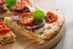 Stück Pizza mit Salami und Tomaten auf einem hölzernen Brett Lizenzfreie Stockbilder