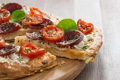Stück Pizza mit Salami und Tomaten auf einem hölzernen Brett Lizenzfreie Stockfotos